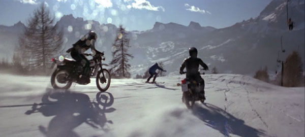 James bond (roger moore) on ski slope hunt by motorcycle enemi